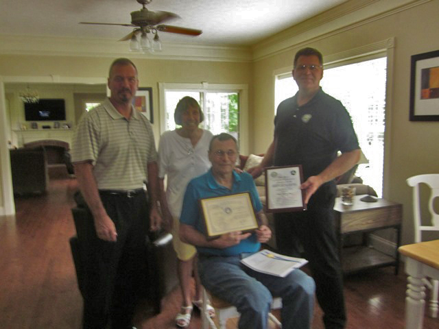 Jerry Peer receives Charles Taylor Award at his home.